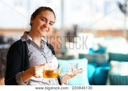 The waitress is carrying tea. Hospitable girl waitress is carrying tea and tea glass teapot to the client in the restaurant. The concept of maintenance and service.