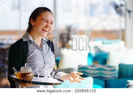 The waitress is carrying tea. Hospitable girl waitress holding tray with cup of tea and tea glass teapot for the client at the restaurant. The concept of maintenance and service.