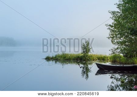 Row boat in the morning light by a misty lake