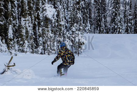 A snowboarder carving down the mountain on Blacktail Mountain in Montana