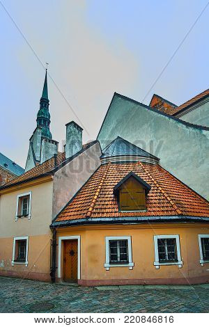 Old medieval evening narrow street with Saint Peters Lutheran church on the background in Riga Latvia. Retro styled.