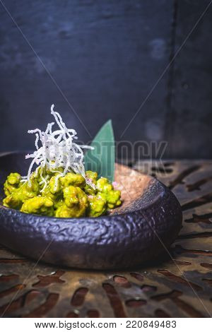 The food of molecular cuisine on an iron plate. Food sipped with green sauce lies on a dark plate. The dark plate is on the table. Pasta from transparent substance decorates the food.