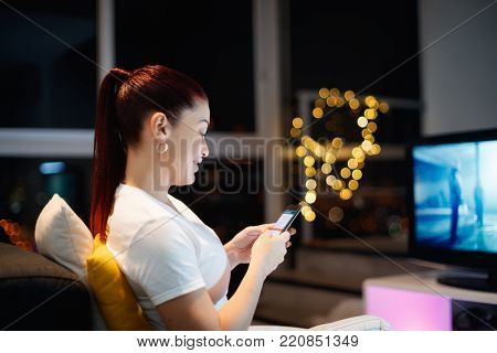 Mid adult woman sitting on sofa at night, chatting with mobile phone in slow motion. 40 years old latin american woman sending message on social network with smartphone, with TV in background