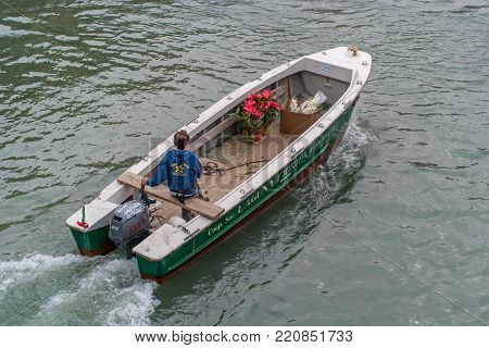 Venice, Italy - October 13, 2017: Boat for delivery of flowers swims to fulfill the order. The boat is run by an employee in branded clothes. View from above. In the boat there are flowers.