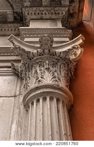 Decorative capital of column. White column against the background of an orange wall.