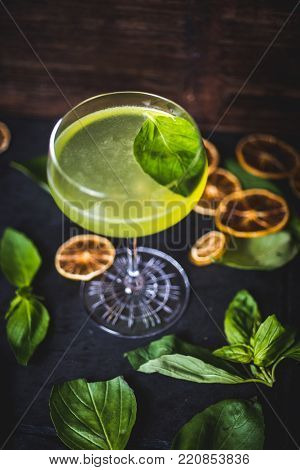 A carbonated cocktail with a mint leaf in a glass. Top view of a floating mint leaf in a cocktail. Cocktail on the background of falling lemon slices. Fouger stands on a table among the lying leaves of mint. A view of the cocktail in a wine-glass on the t