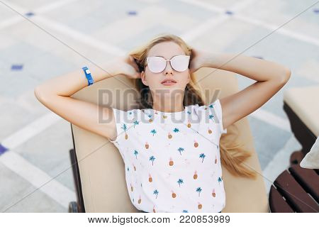 Attractive Woman In Sunglasses Is Lying On A Chaise-lounge Near Swimming Pool On Summer Time