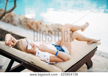 Woman Relaxing On Chaise-lounge By The Pool