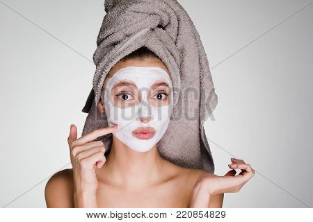 a surprised young girl with a towel on her head applied a white nutritious mask to her face