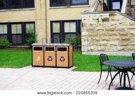 JOLIET, ILLINOIS / UNITED STATES - JULY 26, 2017: Garbage receptacles, for recycling and landfill, are available on the Quad, outside Donovan Hall, at the University of Saint Francis.