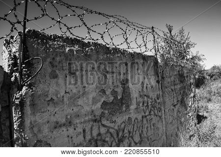 Barbed wire on cement fence. Monochrome silhouette photo