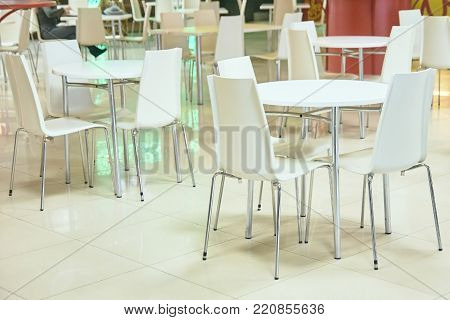 Food court. White tables and chairs. Bright interior.