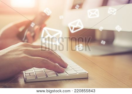 Email marketing and newsletter concept, Hand of man sending message and mobile phone with email icon