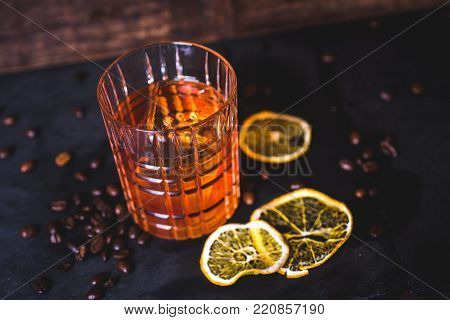 Top view of a drink with ice in a crystal glass. Close-up of alcohol in a glass. Whiskey or bourbon is poured into a glass. Dried lemon slices and coffee grains lie on the table.