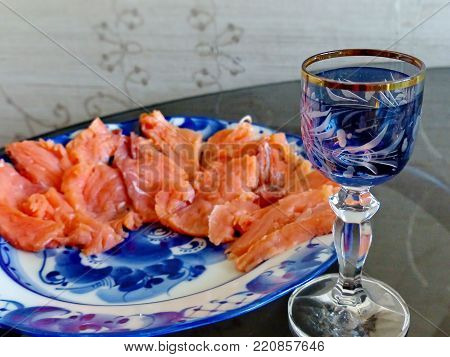 Wineglass of of cold vodka and sliced salmon on a plate Gzhel. Natural food, appetizer. Gorgeous home appetizer under a glass of vodka.Gzhel - Russian folk craft of ceramics and production porcelain