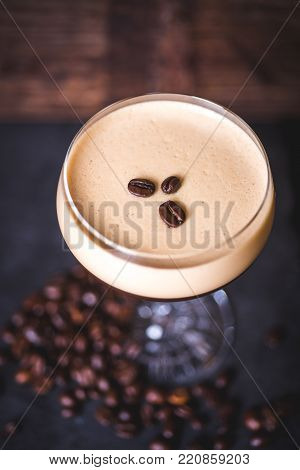 Top view of the coffee beans lying on the foam cocktail. Coffee beans lie on the table near the wine glass.