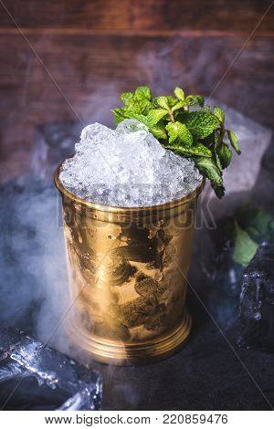 Crushed ice in a tin can on the table. Ice cubes lie in the background. A tin can with ice is decorated with a sprig of mint. Light smoke envelops the bucket.