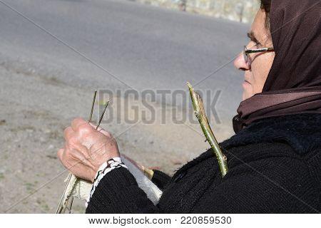 Masuleh, IRAN - December 22, 2017 close up portrait of an elderly woman knitting woolen sock when she care sheep beside road. Gilan Province