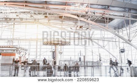 Bright contemporary waiting hall of glass and chrome airport terminal with multiple people inside; modern metallic and white interior or train depot station with huge windows facade in background