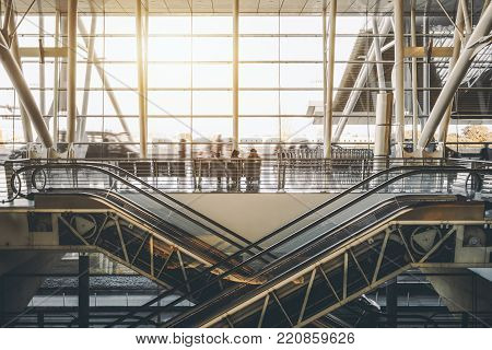 View of two crosswise modern escalators with visible inner mechanisms and gears located in bright contemporary hall of modern airport terminal or train depot station with huge glass facade behind