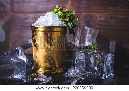 A container with ice stands among ice cubes and mint. A small iron bucket stands on a table with ice. Ice cubes lie in the background.
