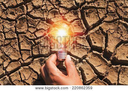 hand holding light bulb on soil arid. concept power solar energy in nature