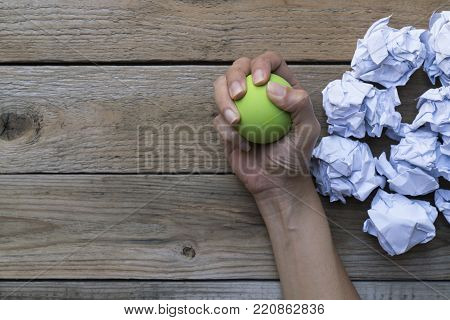 Hand of a woman squeezing a stress ball with crumpled paper