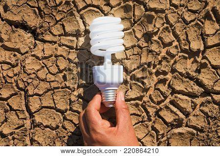 hand holding light bulb on soil arid. concept power solar energy