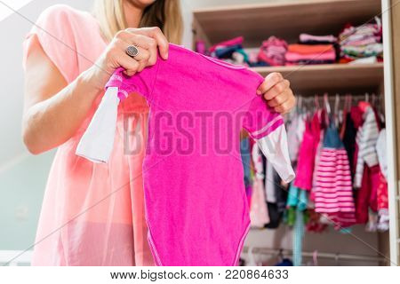 Soon-to-be mom shows girls clothes with anticipation in baby room