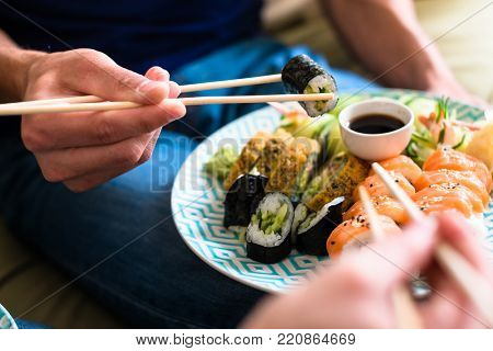 Close-up of the hands of a young couple eating traditional Japanese food with chopsticks during romantic dinner at home