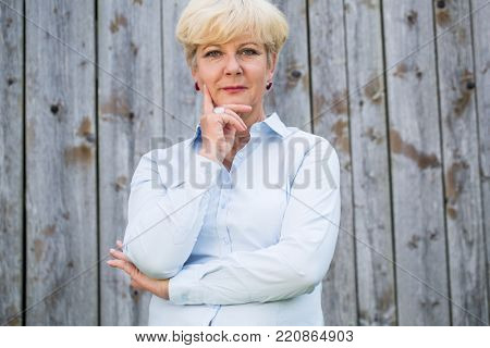 Portrait of an active senior woman looking at camera with a serene and pensive facial expression while posing against an old rustic fence