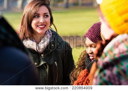 Self-confident young woman surrounded by multi-ethnic friends outdoors in a cold day of winter