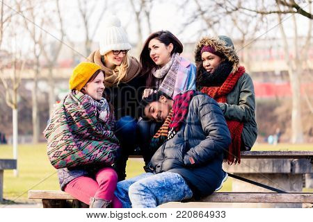 Multi-ethnic group of beautiful young people sitting together in the park in a cold day