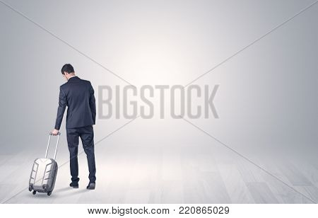Young businessman in a white boundless space walking with back and luggage on his hand
