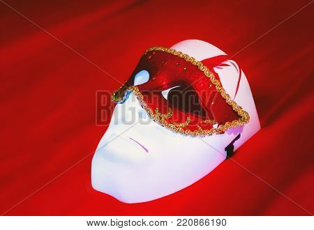 Masquerade mask lies on a white plastic mask closeup on a red silk background. Selective focus, space for copy.