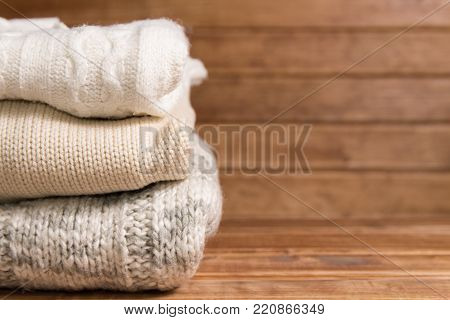Stack Of Cozy Knitted Warm Sweater ,wooden Background . Sweaters In Retro Style.