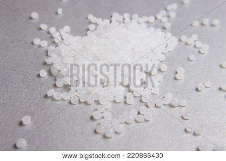 Polypropylene transparent granules on the grey background.