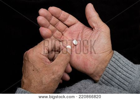 Pensioner Holds A Lot Of Colored Pills In Old Hands. Painful Old Age. Health Care Of Older People