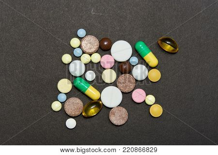 Opioid epidemic .Opioid Pills. Drug abuse Concept - different colored pills on a black background.