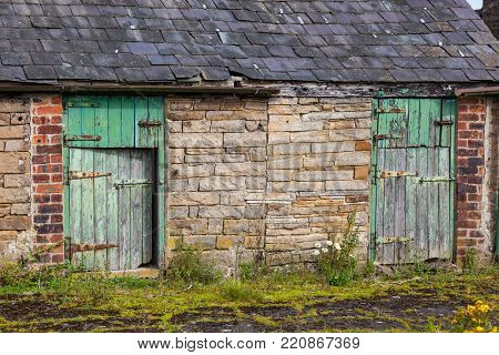 An old stone barn with colorful wooden doors in Northumberland in England.
