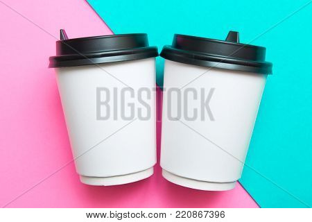 Two disposable cups for hot drinks on a pink and mint geometric backgrounds. Trend colors.