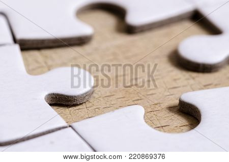 white jigsaw/puzzle with one gap, over wooden table background, symbol of problem solving
