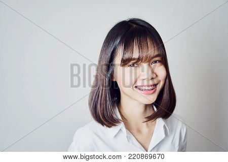 copy space portrait of smiling asian young woman put on the braces, on a gray background gives a soft light.