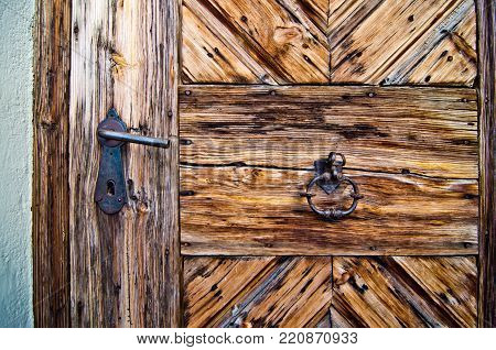 locking mechanism and knocker  in burnished metal of an ancient wooden door