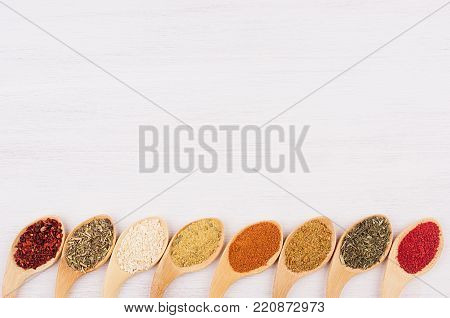 Asian spices in wooden quaint spoons on soft white board.