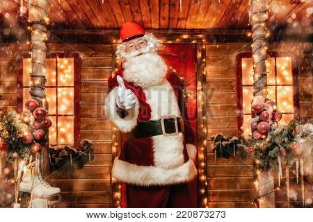 Santa Claus is a builder. House of Santa Claus. Portrait of Santa Claus in a helmet on his head standing near his decorated house and shows the thumb. Christmas and New Year concept.