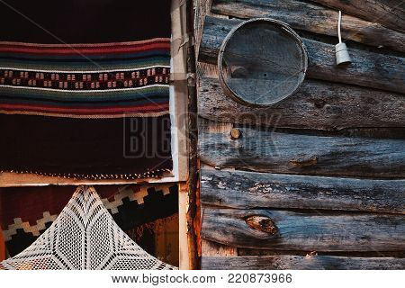 Various textures of a wooden house. Details of old embroided decorative blanket and wooden wall with souvenirs.