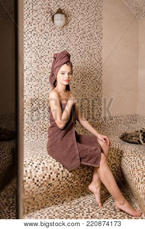 Attractive woman relaxing in a hammam - turkish steam bath with ceramic tile in roman style.