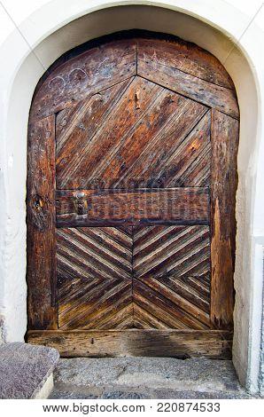 antique wooden door with knocker and burnished metal locking mechanism poster