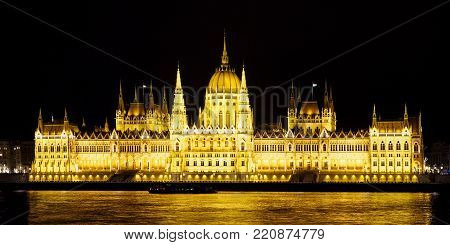 Iluminated Hungarian parliament on Danube riverside by night in Budapest. Travel destinations. poster